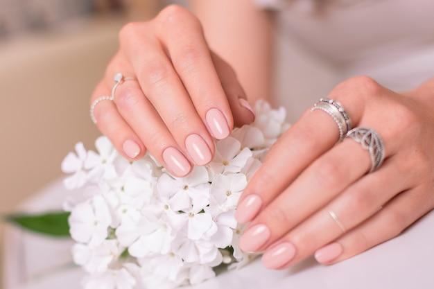 結婚式のマニキュアの爪、ヌードジェルポリッシュ、白い花を持つ女性の手