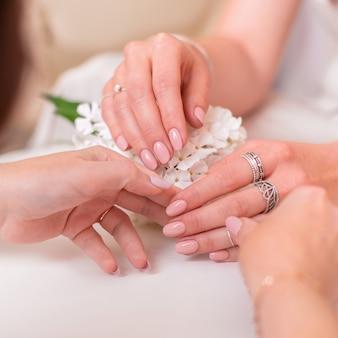 結婚式のマニキュアの爪を持つ女性の手