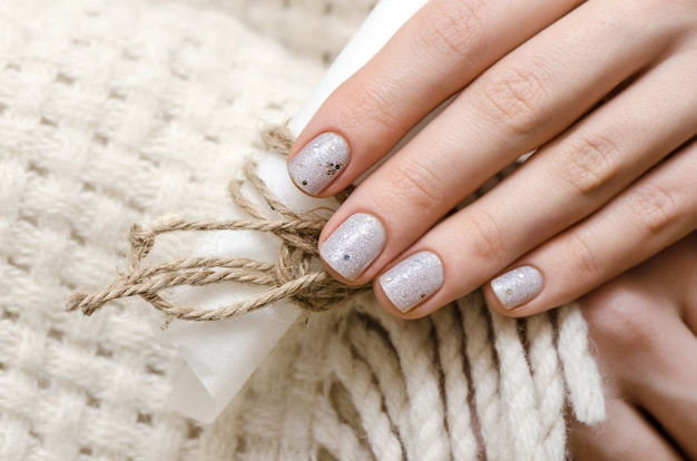 Female hands with white glitter nail design.