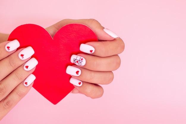 Женские руки с белым маникюром, ногтями, дизайном сердец