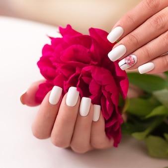 白いマニキュアネイル牡丹デザインの女性の手