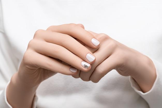 Женские руки с белым дизайном ногтя, крупным планом.