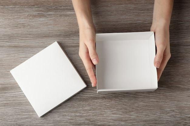 Женские руки с белой открытой коробкой на деревянной поверхности