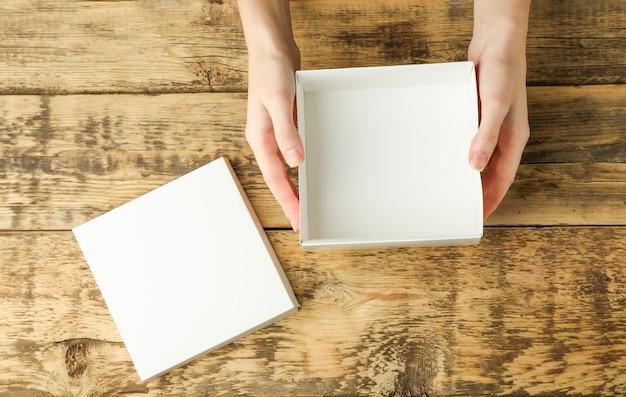 Женские руки с белой открытой коробкой на деревянном столе