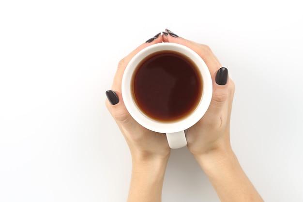 Женские руки с видом сверху чашки белого чая