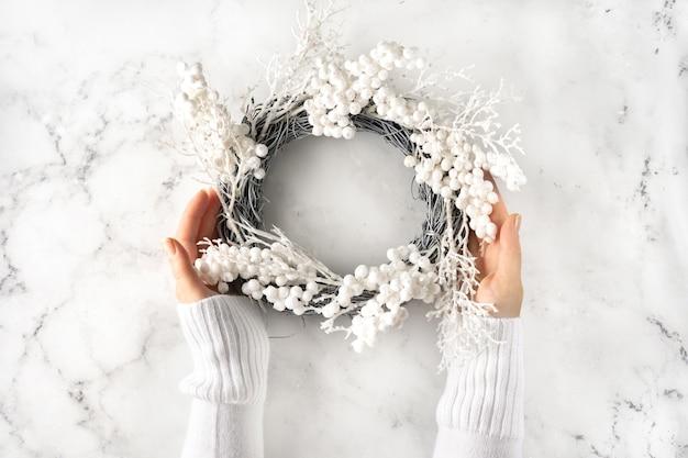 大理石の背景にクリスマスリースを保持している白い暖かい葉の女性の手。冬の休日のコンセプト