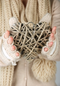 枝編み細工品の心を持つ女性の手、クローズアップ