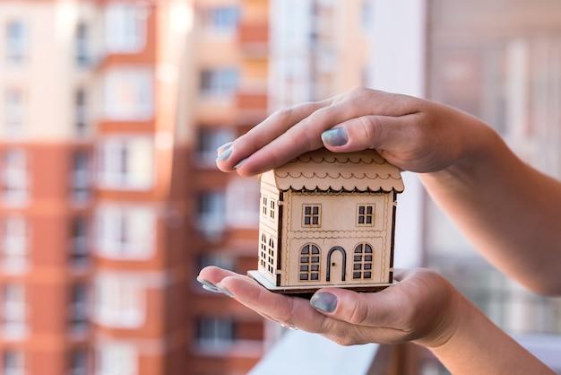 Женские руки с моделью деревянного дома на фоне строительной площадки