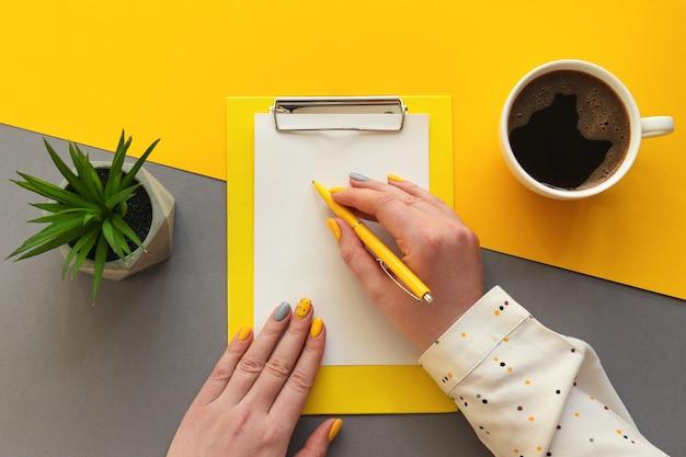 紙に書く女性の手クリップボードのコーヒーと多肉植物のある職場