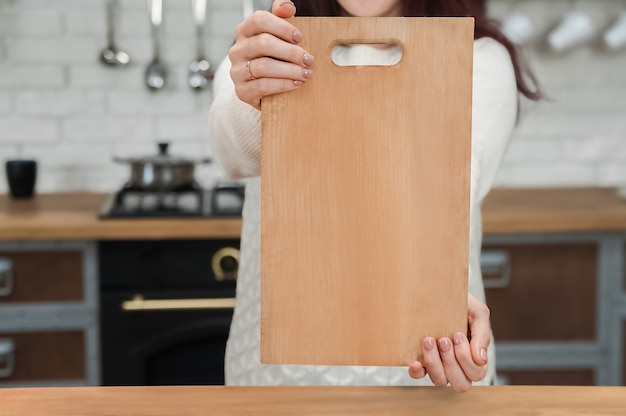 Female hands and wooden board close-up.