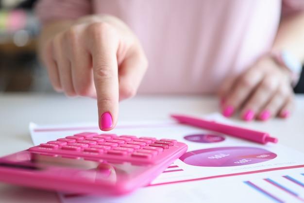 女性の手はペンとビジネスチャートの近くで計算機を動作させます