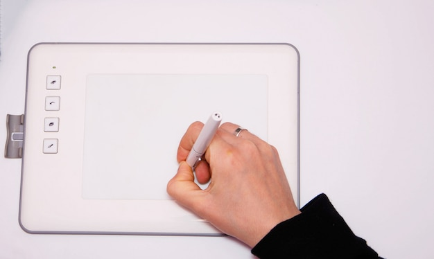 여성 손 그래픽 태블릿에서 작동합니다. 손은 스타일러스 펜을 잡고 그립니다