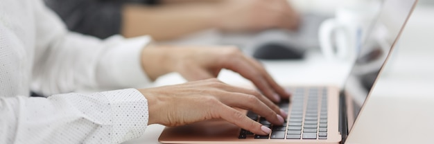 女性の手はオフィスのラップトップで動作します。学習と教育のコンピュータコースの概念