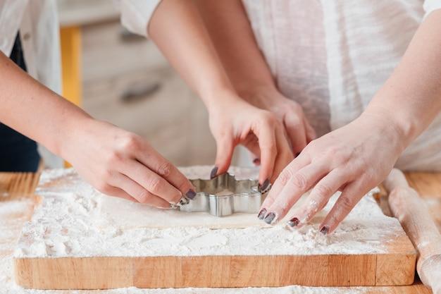 쿠키를 만들기 위해 반죽을 사용하는 여성 손
