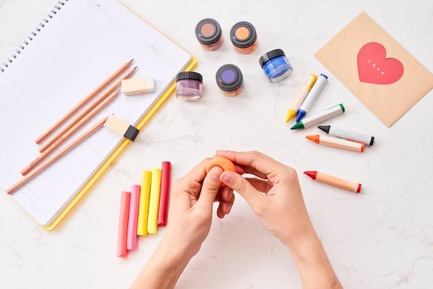 Женские руки работают с полимерной глиной. процесс работы с пластиком на белом фоне.