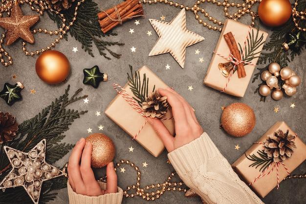 여성 손 나무 테이블에 크리스마스 장식과 선물 포장. 평면도