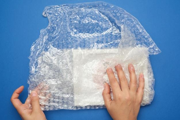 泡で透明なプラスチックラップでアイテムを包む女性の手