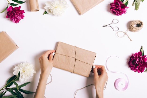 Female hands wrapping presents on white table