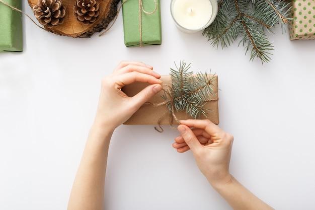 Женские руки оборачивают коробку с рождественским подарком на белом столе с рождественскими украшениями. рождество зима новый год концепция нулевых отходов