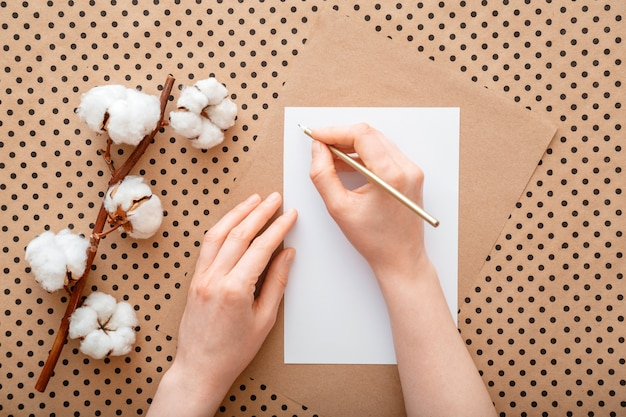 Female hands write letter on table with cotton blooming flowers. woman make wish list or to do list flat lay. girl writes sign greeting card.