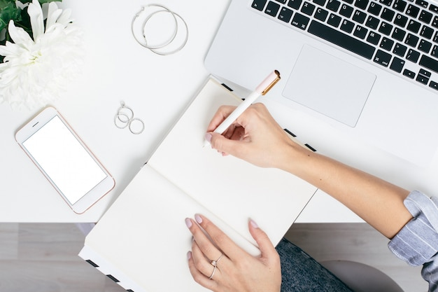 Female hands write in notebook on a white table with a keyboard and blank screen phone