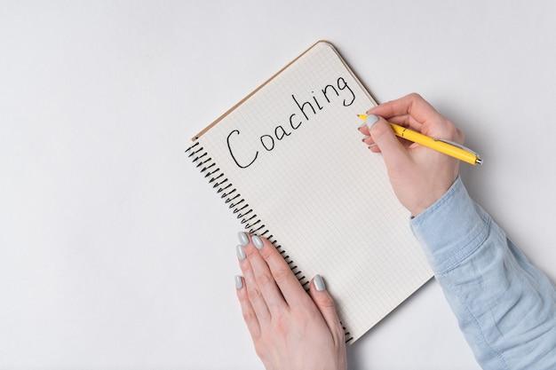 女性の手は、メモ帳で「コーチング」という単語を書き込みます。白色の背景。上面図