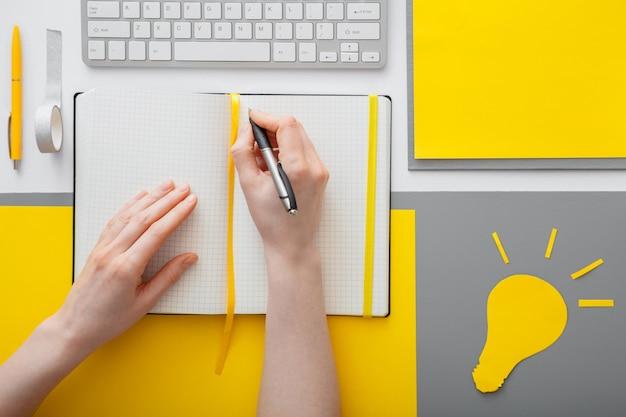 작업 공간의 데스크탑에 있는 빈 노트북에 아이디어 목표를 쓰는 여성 손. 여자는 회색 노란색 배경에 노트북에 아이디어 목록을 씁니다. 노란색 전구 아이디어는 유입니다.