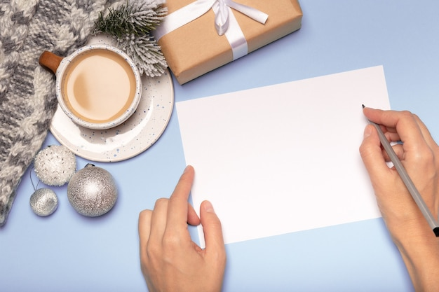 Female hands writing christmas card, paper gift box and coffee on blue background