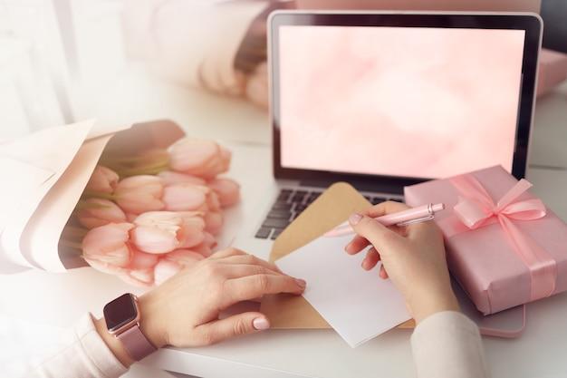 机の上のギフトボックスとラップトップ、上面図でバレンタインや誕生日の後者の紙に願いを書き留める女性の手。