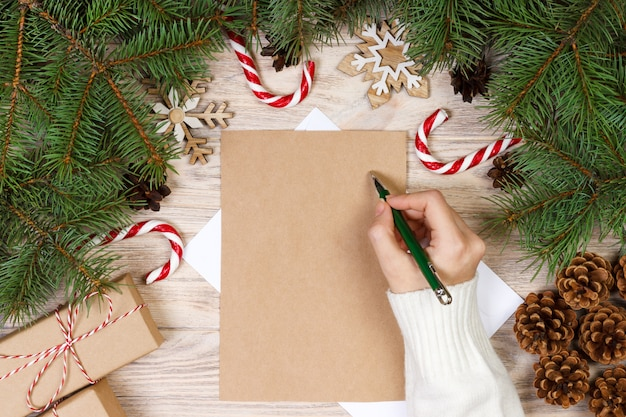 Female hands writing a letter to santa claus, christmas gifts on wood.