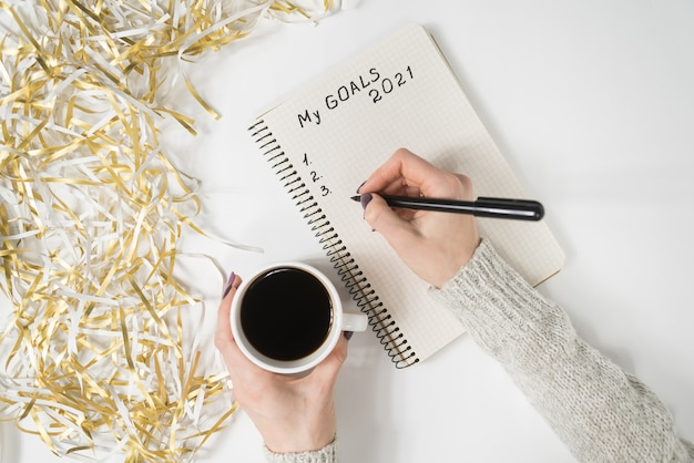 Female hands writing my goals 2021 in a notebook. mug of coffee on the table, top view.