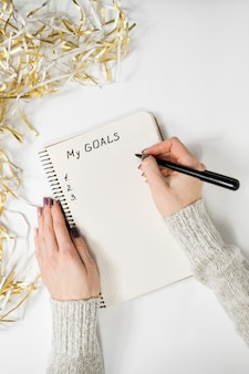 Female hands writing my goals in a notebook, tinsel, new years concept
