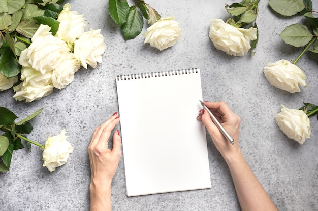 Female hands writing in notebook and bouquet white roses on grey. top view with copy space.