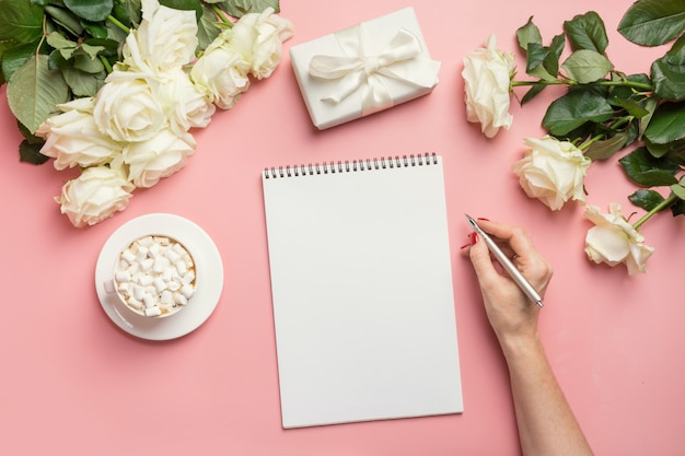 Female hands writing in notebook and bouquet white roses on pink. top view with copy space.