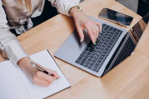 Mani femminili che scrivono sul blocco note e lavorano al computer