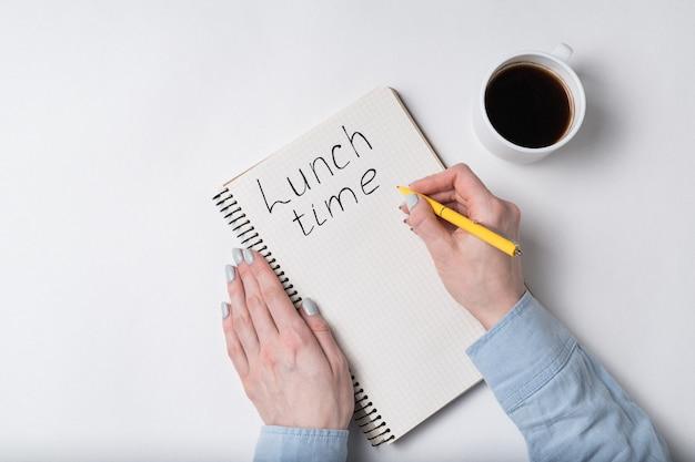 Женские руки писать слова время обеда. тетрадь и чашка кофе на белой предпосылке.