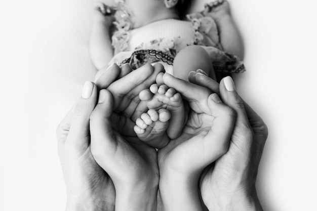 Female hands of young mother holding her baby feet, closeup image with blur baby in background. high quality photo