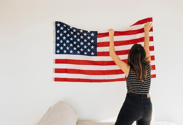 Female hanging national flag on wall