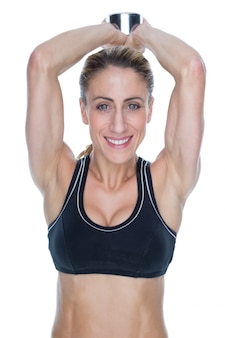 Female happy bodybuilder working out with large dumbbell behind head