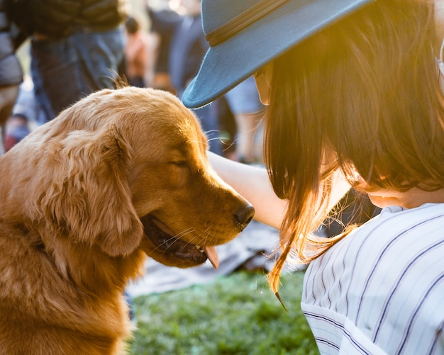 Female in a hat petting an adorable cute brown retriever dog