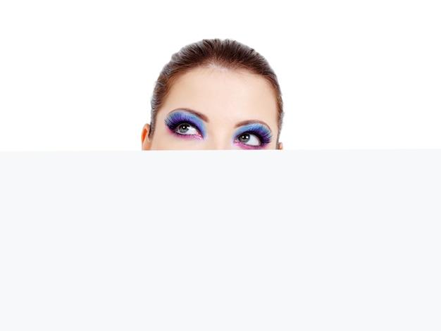 Testa femminile con begli occhi che guardano da una bandiera bianca in bianco