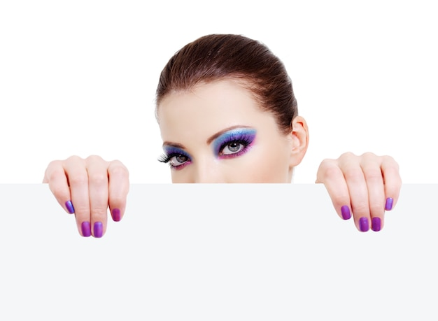 Female head with beautiful eyes looking out of a blank white banner