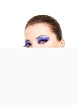 空白の白いバナーから見ている美しい目を持つ女性の頭