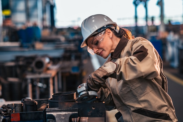 Female heavy industry worker in protective work wear grinding metal.
