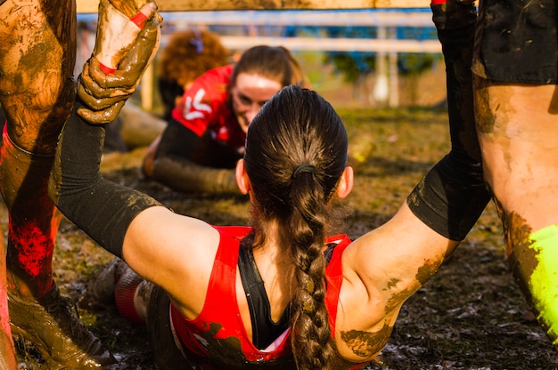 Female helped by a helping hand on a xtreme mud race