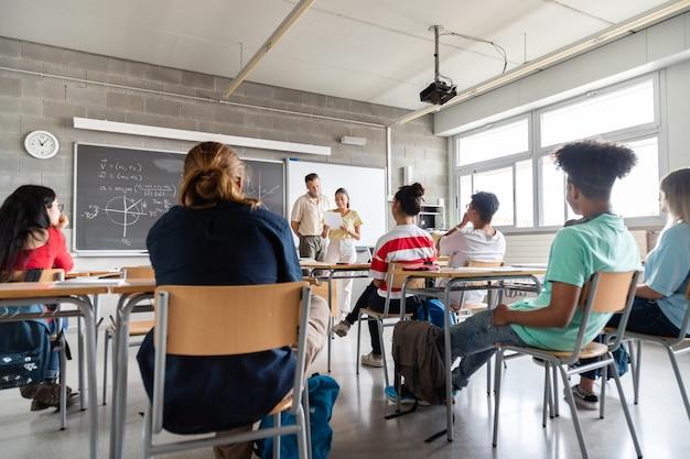 Ученица старшей школы проводит презентацию для одноклассников, принадлежащих к разным расам. копирование пространства образование