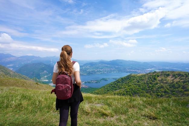 ベルヴェデーレから山をトレッキングした後、風景を楽しむ女性ハイカー