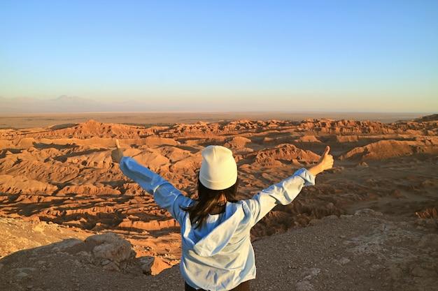 Female hiker excited with the moon valley or valle de la luna in atacama desert