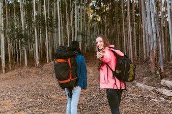 Female hiker gesturing while walking with her friend in forest