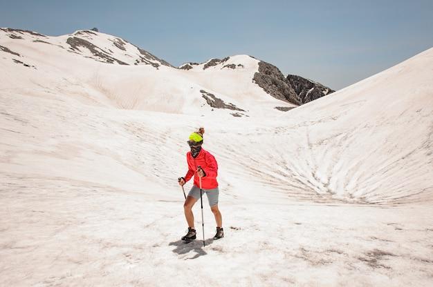 山の赤いジャケットの女性ハイカー